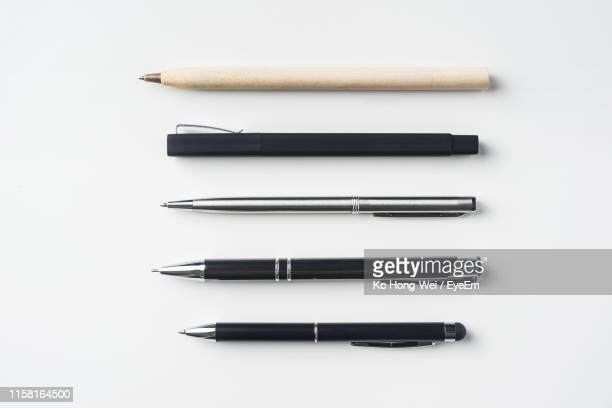 directly above view of pens against white background - kugelschreiber stock-fotos und bilder
