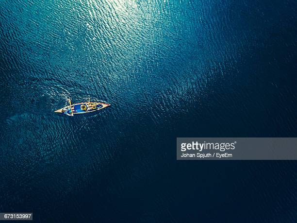 directly above view of people rowing boat in sea - kanu stock-fotos und bilder