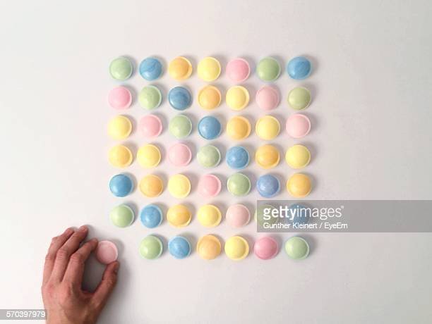 Directly Above View Of Person Arranging Candies Against White Background