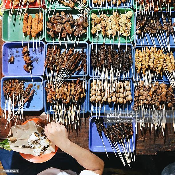 directly above view of person eating skewer meat at market stall - yogyakarta stock pictures, royalty-free photos & images