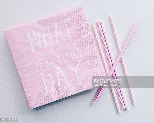 Directly Above View Of Pink Napkins With Striped Straws On Table