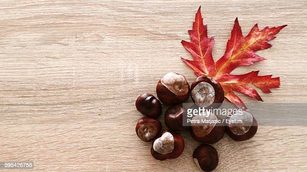 Directly Above View Of Red Autumn Leaf And Chestnuts On Table