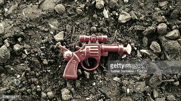 Directly Above View Of Red Toy Gun Amidst Rocks