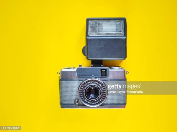 directly above view of retro vintage camera and speedflash on yellow background - movie camera stock pictures, royalty-free photos & images