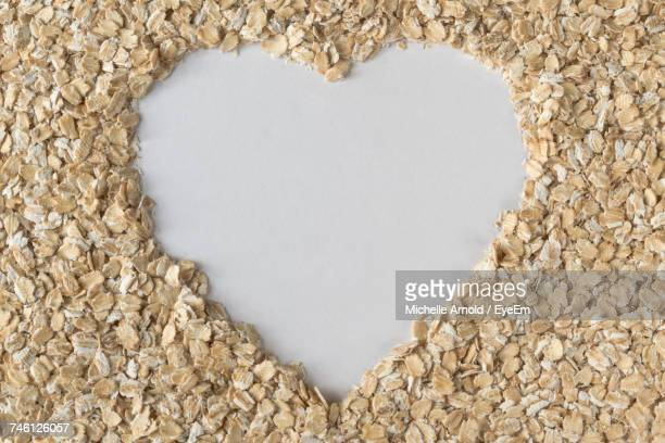 Directly Above View Of Rolled Oats Arranged As Heart Shape On White Table