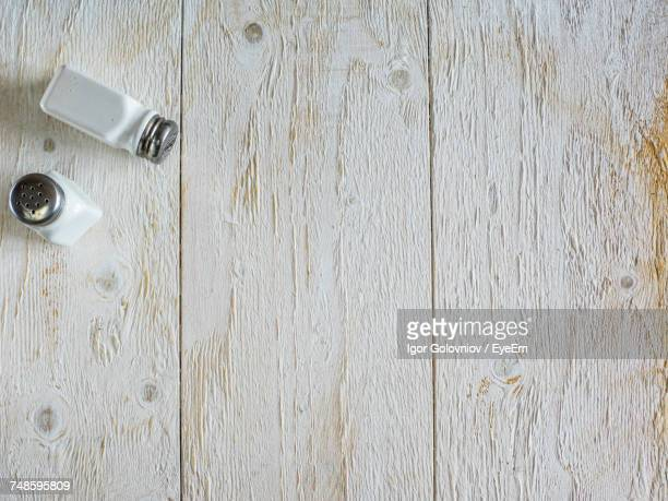directly above view of salt and pepper shakers on wooden table - igor golovniov stock pictures, royalty-free photos & images
