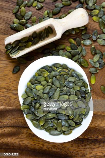 directly above view of scoop on pumpkin seeds. - organic compound stock photos and pictures