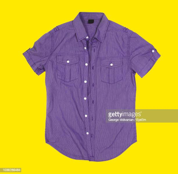 directly above view of shirt on yellow background - purple shirt stock photos and pictures