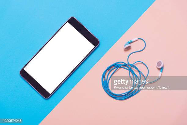 directly above view of smart phone and in-ear headphones against colored background - ツートンカラー ストックフォトと画像