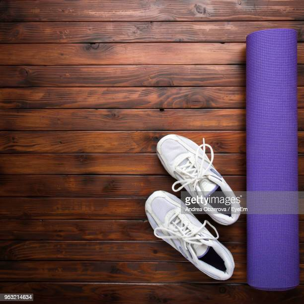 directly above view of sports shoes by yoga mat on hardwood floor - purple shoe stock pictures, royalty-free photos & images