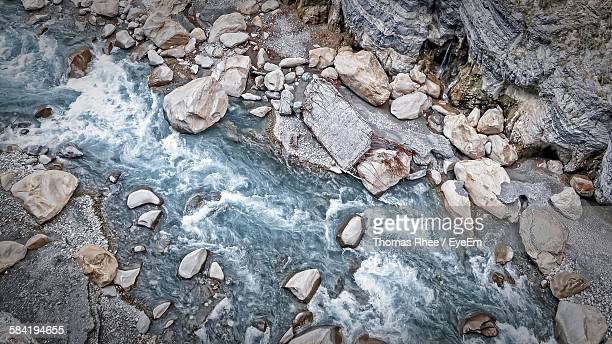directly above view of stream amidst rocks - bach stock-fotos und bilder