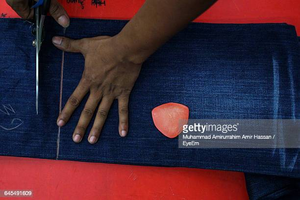Directly Above View Of Tailor Cutting Jeans On Table At Workshop