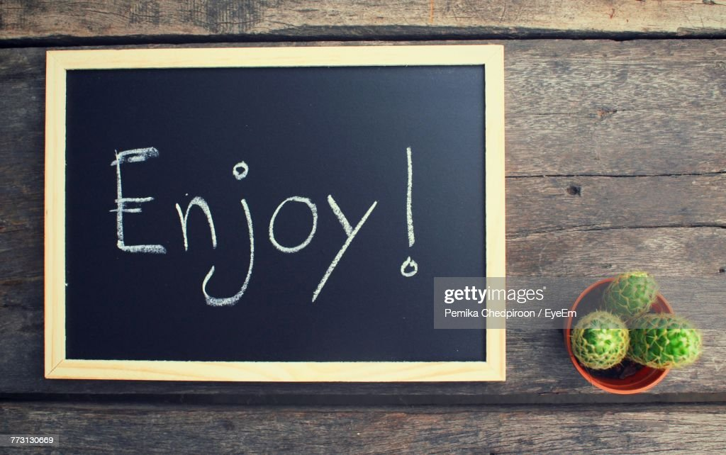 Directly Above View Of Text Over Blackboard By Cactus On Table : Photo