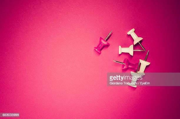 Directly Above View Of Thumbtacks On Pink Background