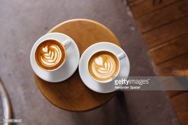 directly above view of two coffee cups with latte art on the round table - kaffee stock-fotos und bilder