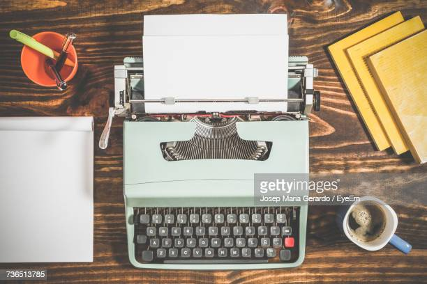 Directly Above View Of Typewriter Amidst Books And Coffee Cup On Table