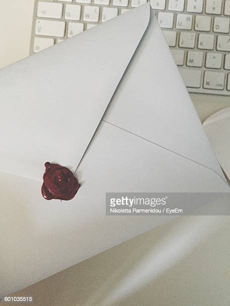 Directly Above View Of White Envelope With Seal Over Laptop On Table