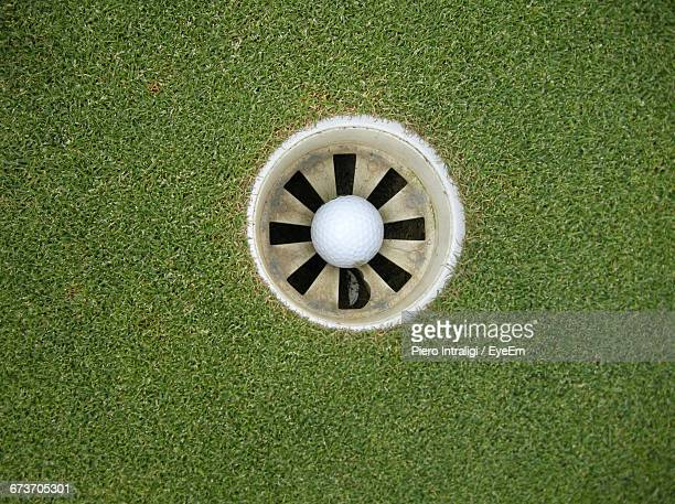 directly above view of white golf ball in hole on course - green golf course stock pictures, royalty-free photos & images