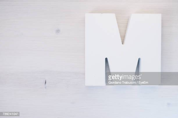 directly above view of white letter m on wooden table - letter m stock pictures, royalty-free photos & images