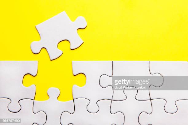 directly above view of white puzzles against yellow background - jigsaw piece stock pictures, royalty-free photos & images