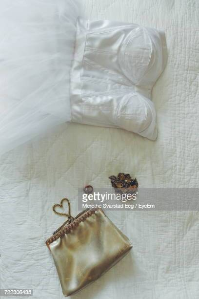 Directly Above View Of White Wedding Dress And Womenswear On Bed