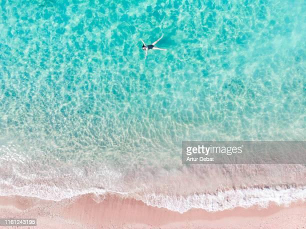 directly above view of woman floating on transparent water in greece. - greek islands stockfoto's en -beelden