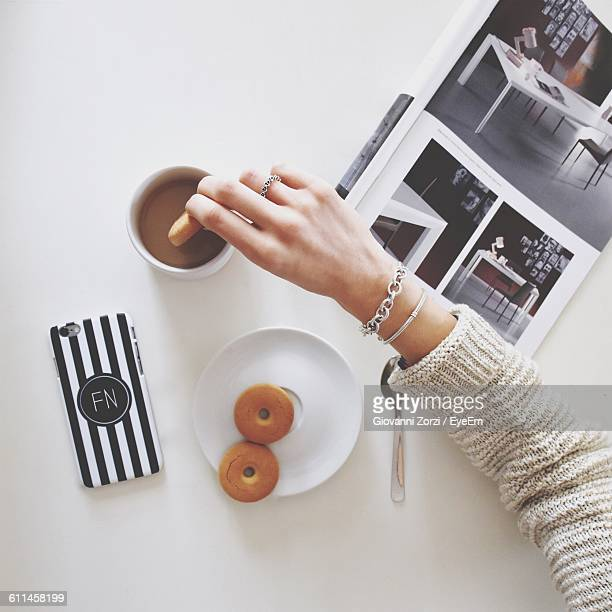 directly above view of woman hand dipping cookie in coffee - dipping stock photos and pictures
