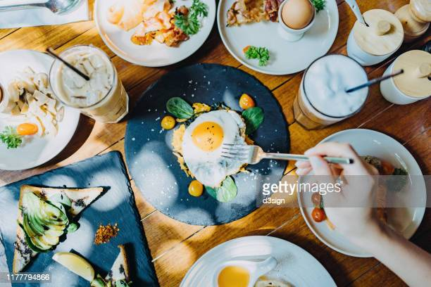 directly above view of woman sharing a variation of meal in an outdoor restaurant against beautiful sunlight - breakfast stock pictures, royalty-free photos & images