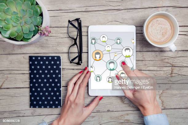 Directly Above View Of Woman Using Digital Tablet On Table