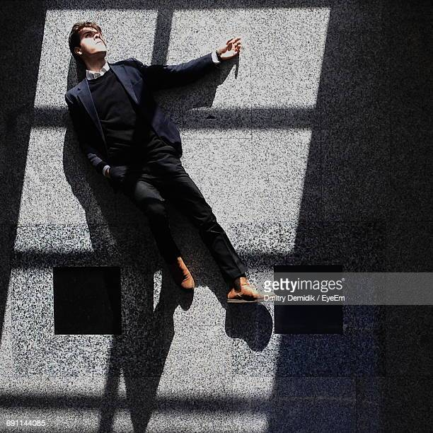 Directly Above View Of Young Businessman Lying On Tiled Floor