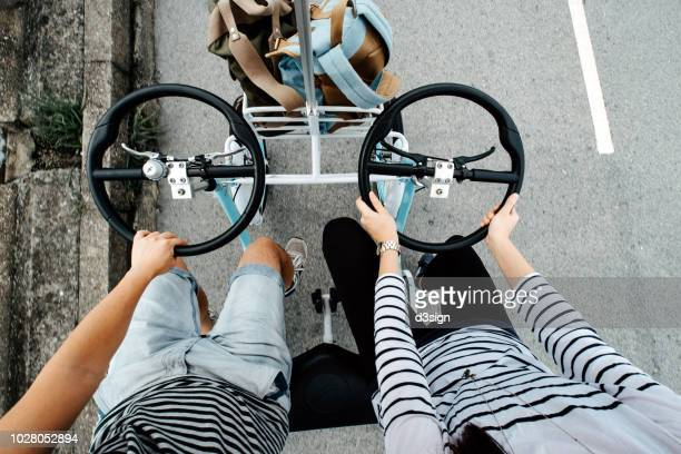 directly above view of young couple riding bicycle joyfully on a boardwalk - tandem bicycle stock pictures, royalty-free photos & images