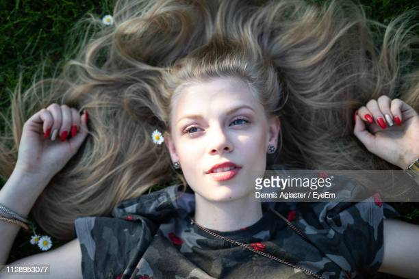 Directly Above View Of Young Woman Lying On Field