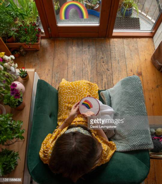 directly above viewpoint of a lady embroidering a gay pride rainbow in support of lgbtqi+ pride at home. - needlecraft stock pictures, royalty-free photos & images
