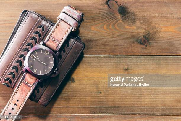 directly above wallet and wrist watch on table - wrist watch stock pictures, royalty-free photos & images