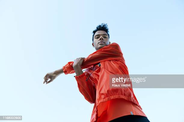 directly below portrait of athlete stretching arm against clear sky - warming up stock pictures, royalty-free photos & images