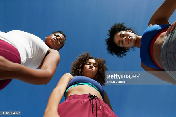 directly below portrait of female athletes standing on sunny day - attitude stock pictures, royalty-free photos & images