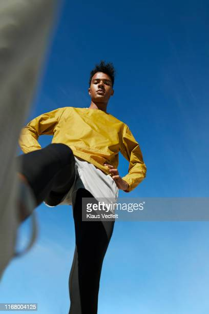 directly below portrait of sportsman against clear sky - yellow trousers stock pictures, royalty-free photos & images