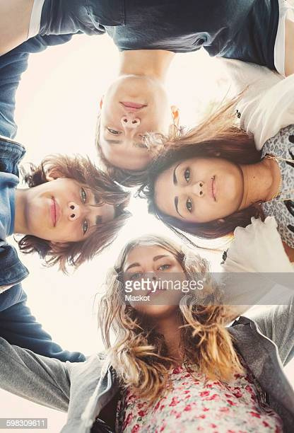 Directly below portrait of teenagers forming huddle against sky