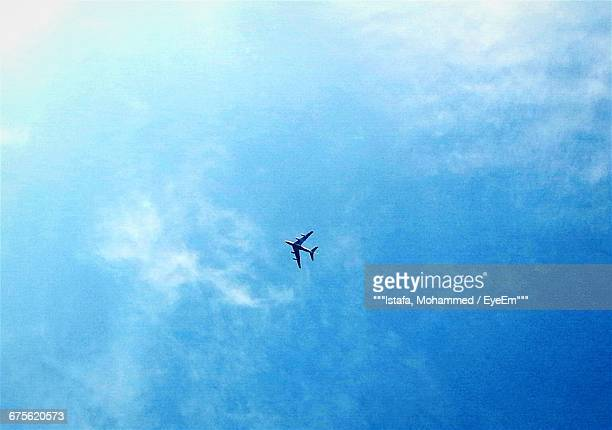 Directly Below Shot Of Airplane Flying Against Blue Sky