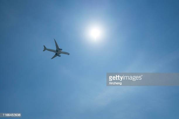 directly below shot of airplane flying in sky - meteorology stock pictures, royalty-free photos & images