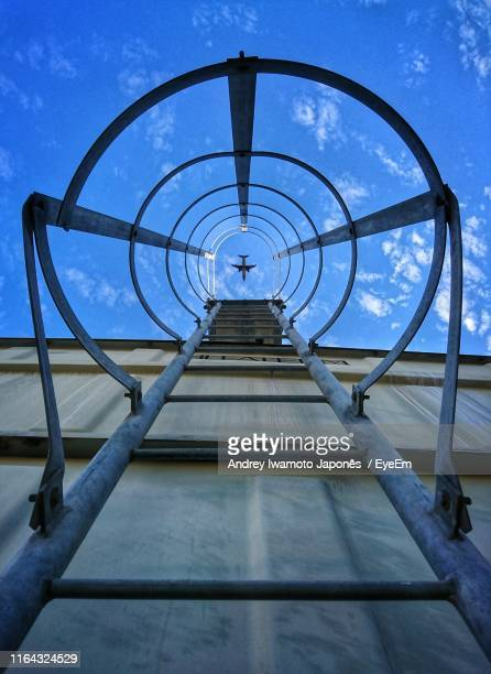 directly below shot of airplane flying over building seen through ladder - japonês stock pictures, royalty-free photos & images