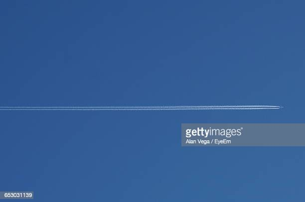 Directly Below Shot Of Airplane Forming Vapor Trail In Blue Sky
