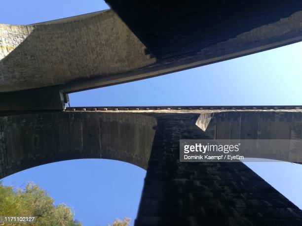 directly below shot of arch bridge against clear blue sky - 人工建造物 ストックフォトと画像