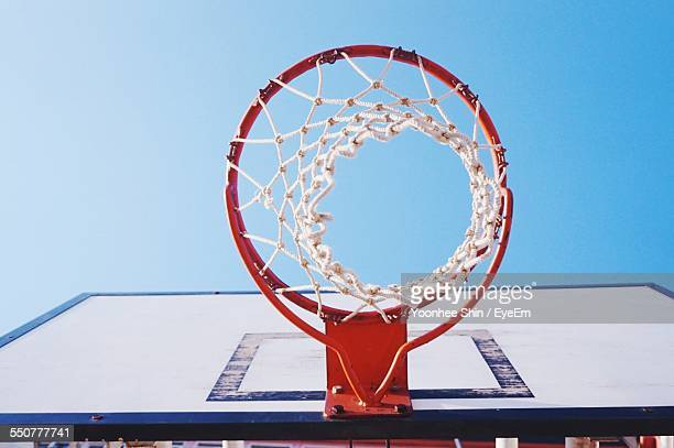 Directly Below Shot Of Basketball Hoop Against Clear Blue Sky