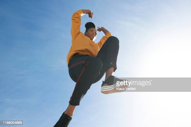 directly below shot of carefree woman jumping against blue sky - blue shoe stock pictures, royalty-free photos & images