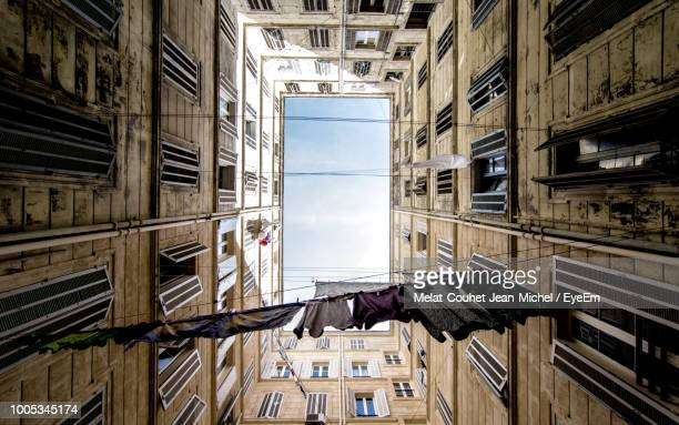 directly below shot of clothes hanging amidst buildings against sky - marseille photos et images de collection