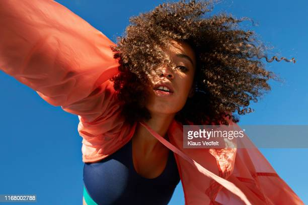 directly below shot of female athlete with curly hair against clear sky - fashion stock-fotos und bilder