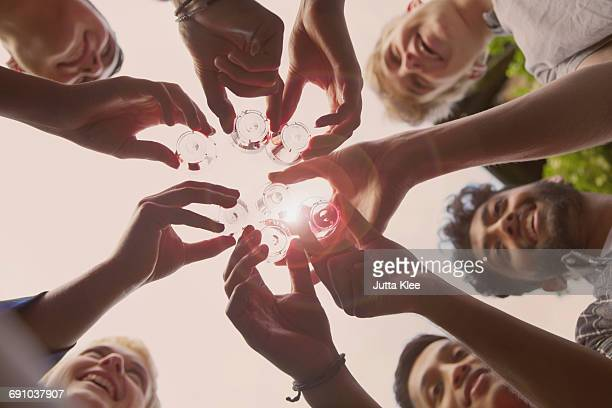 directly below shot of friends toasting tequila shots against sky during summer - asian drink stock photos and pictures