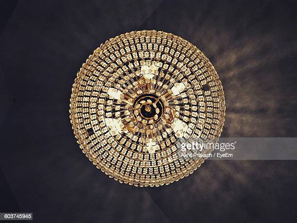 Directly Below Shot Of Illuminated Chandelier Hanging From Ceiling