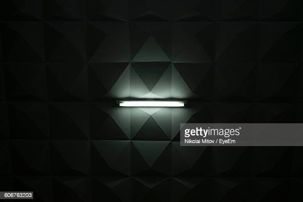 directly below shot of illuminated fluorescent light on ceiling in darkroom - fluorescent light stock pictures, royalty-free photos & images